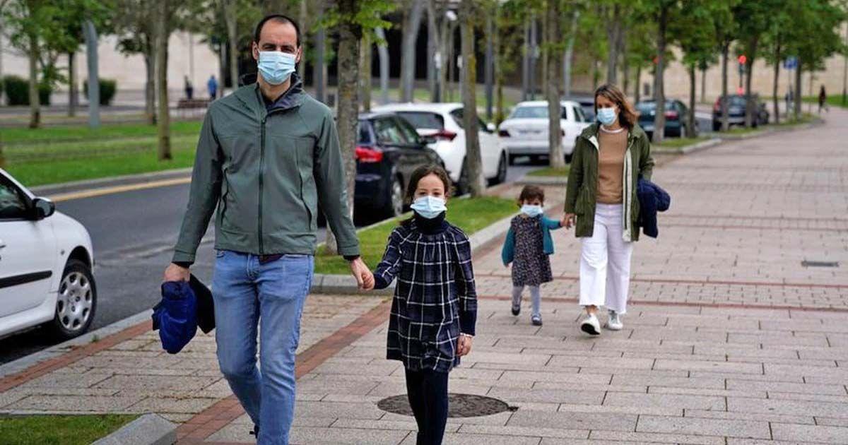 Familia de paseo con mascarillas en plena pandemia del coronavirus