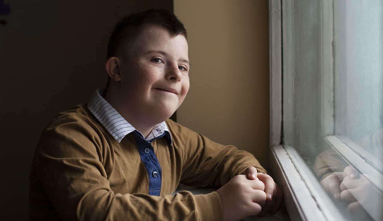 Joven con Síndrome de down en la ventana