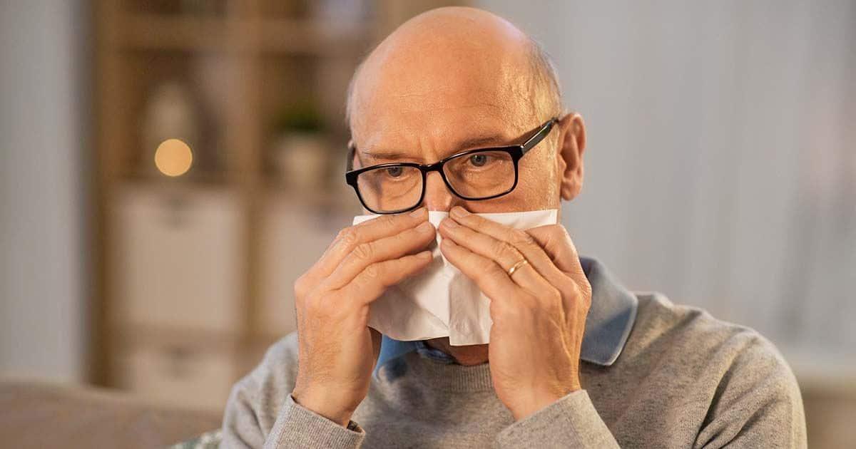 Persona sonándose la nariz olfato