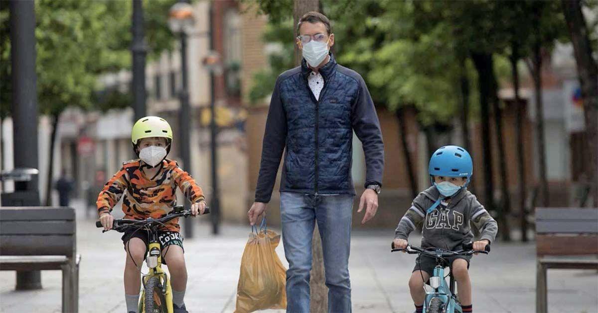 Padre con sus dos hijos dando un paseo en pleno confinamiento