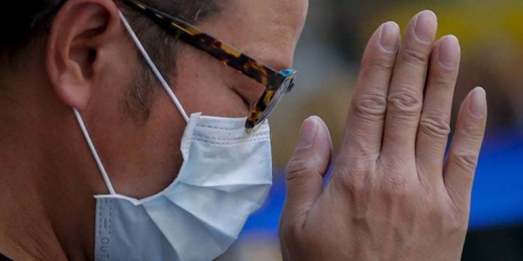 Persona rezando con mascarilla durante la crisis del Coronavirus