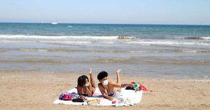 Mujeres toman el sol en la playa con mascarillas en verano