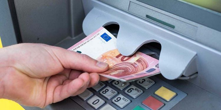 Persona retirando dinero de un cajero Ingreso Mínimo Vital