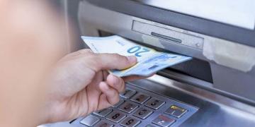 Persona retirando dinero de un cajero para cobrar el paro o ERTE