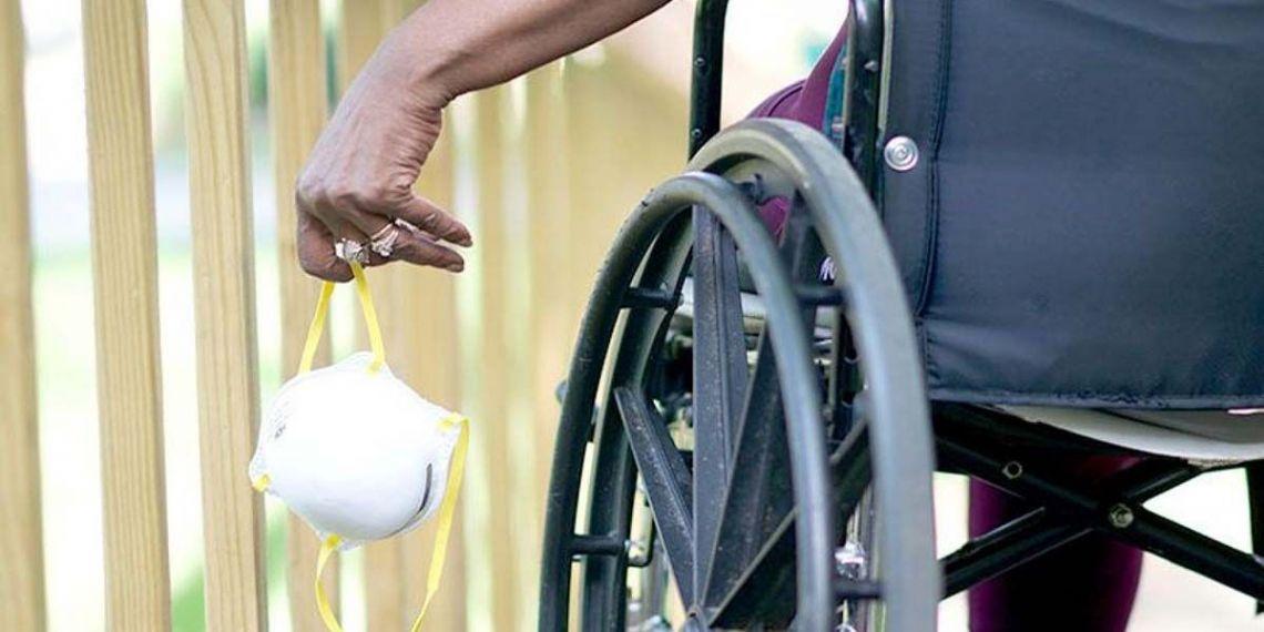 Persona en silla de ruedas con mascarilla