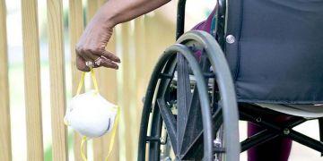 Persona con discapacidad en silla de ruedas con mascarilla soledad mayores