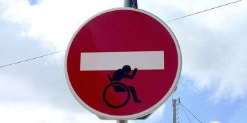 usuario de silla de ruedas aguantando señal de prohibicion