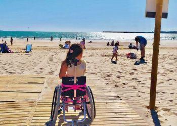 Niña de 7 años en su silla de ruedas en la pasarela playa