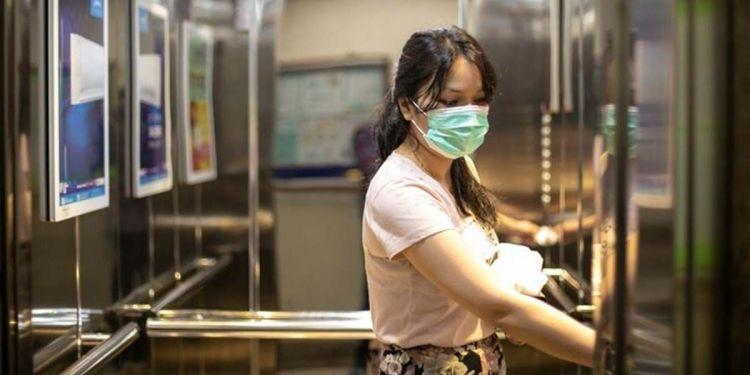Persona con mascarilla protegiendose del Covid-19 cogiendo el ascensor