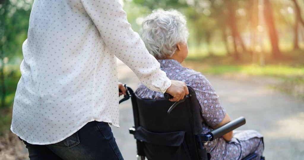 Persona mayor con discapacidad junto con su asistente