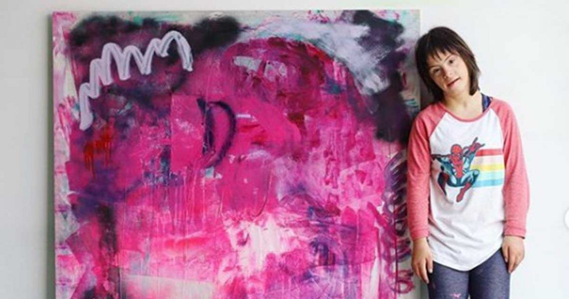 Sevy, artista con síndrome de Down, junto con una de sus pinturas | Foto: Instagram