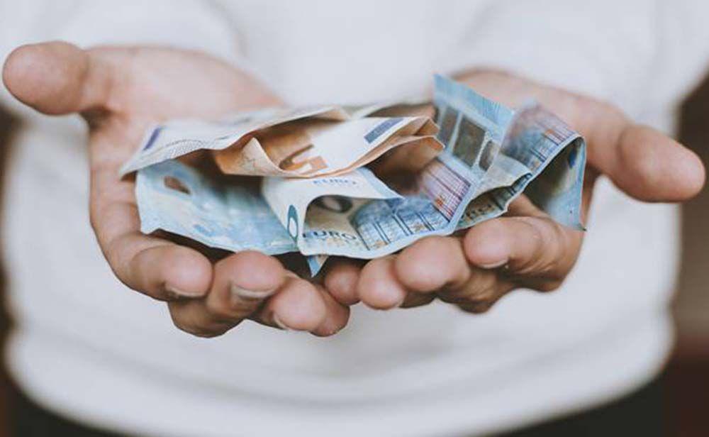Persona con billetes en al mano pensión