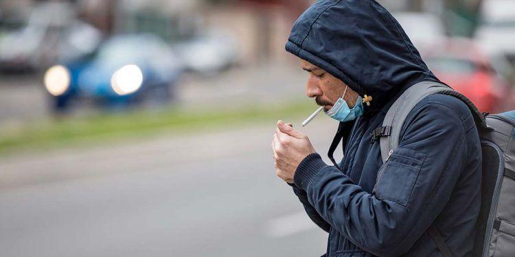 Persona fumando un cigarro con mascarilla