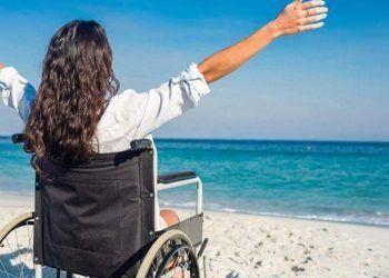 Persona en silla de ruedas en una playa accesible