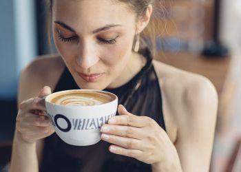 Mujer toma taza de cafe