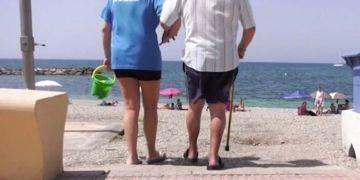Persona con discapacidad siendo ayudada a entrar en la playa de Adra (Almería)