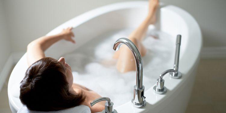 Una mujer dándose un baño caliente