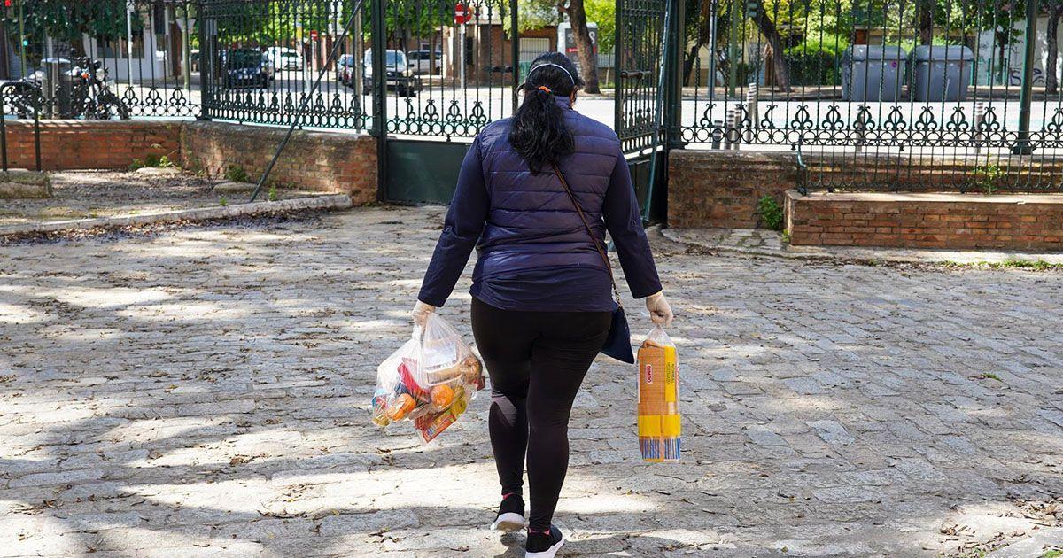 Una mujer con bolsas de la compra durante la pandemia en Sevilla | Foto: EP