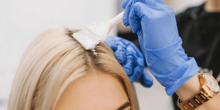 Una mujer recibiendo un tinte en su pelo