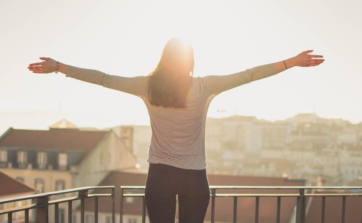 Mujer con brazos abiertos mirando al sol. Calidad de vida