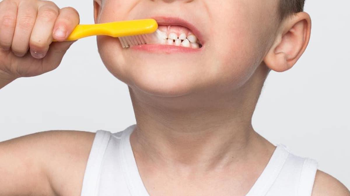 Niño lavándose los dientes con caries