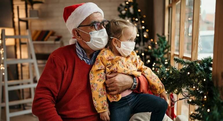 Un abuelo y su nieta con mascarillas durante la Navidad