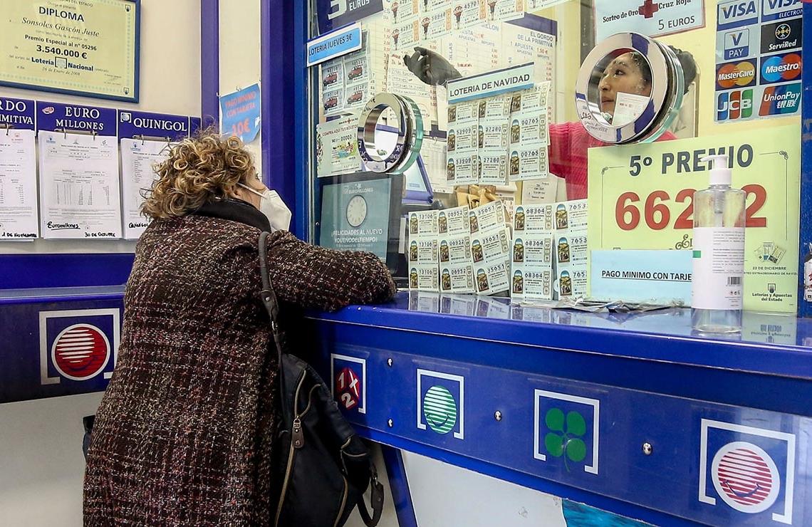 Una mujer comprando un boleto de Lotería de Navidad