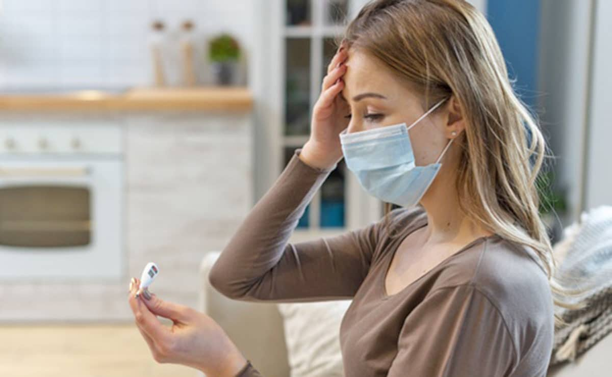 Una persona con mascarilla se toma la temperatura