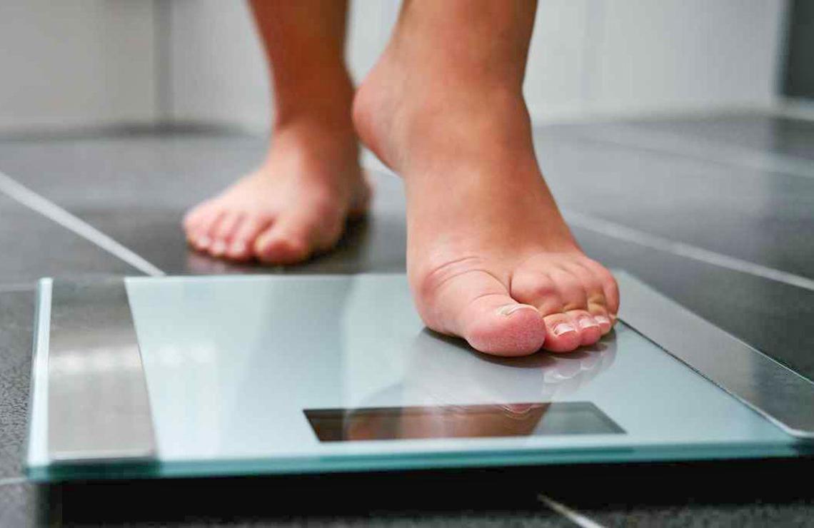 Una persona procede a subir en una báscula para conocer su peso