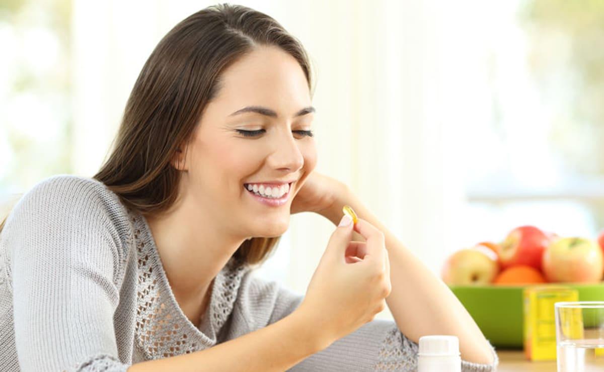 Mujer ingiera un suplemento vitamínico
