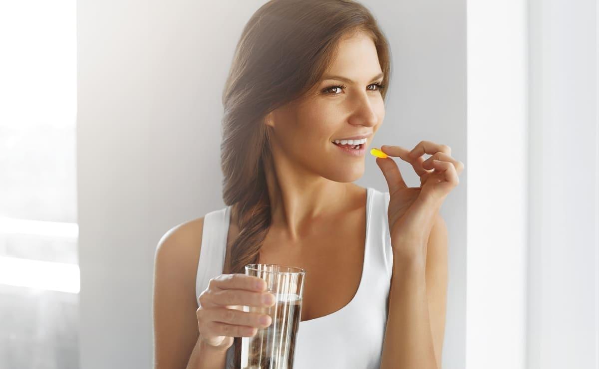 Mujer ingiriendo un suplemento de vitamina E vitamina H