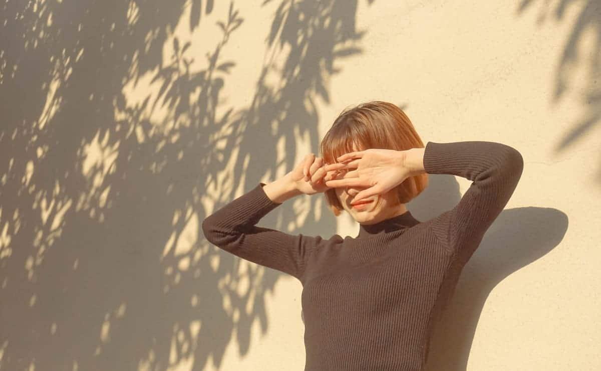 chica ocultándose del sol para protegerse la piel