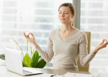 Una mujer con estrés meditando en su puesto de trabajo