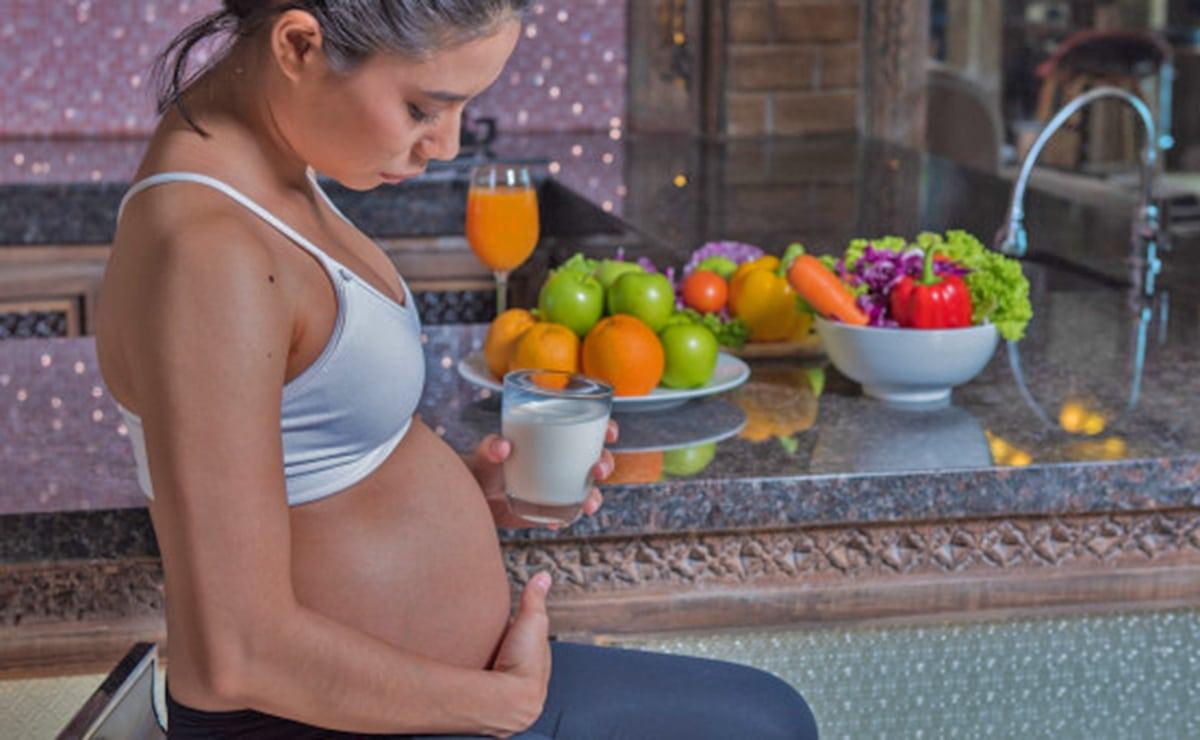Mujer embarazada tomando un vaso de leche