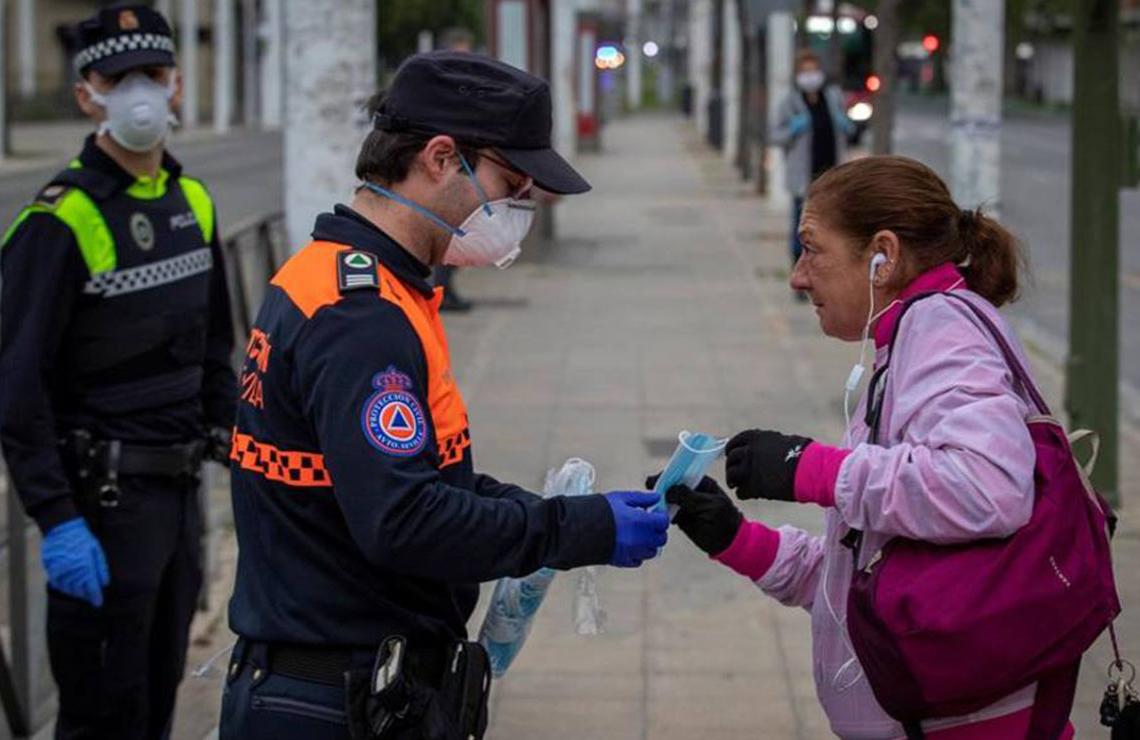 Un policía entregando una mascarilla a una mujer