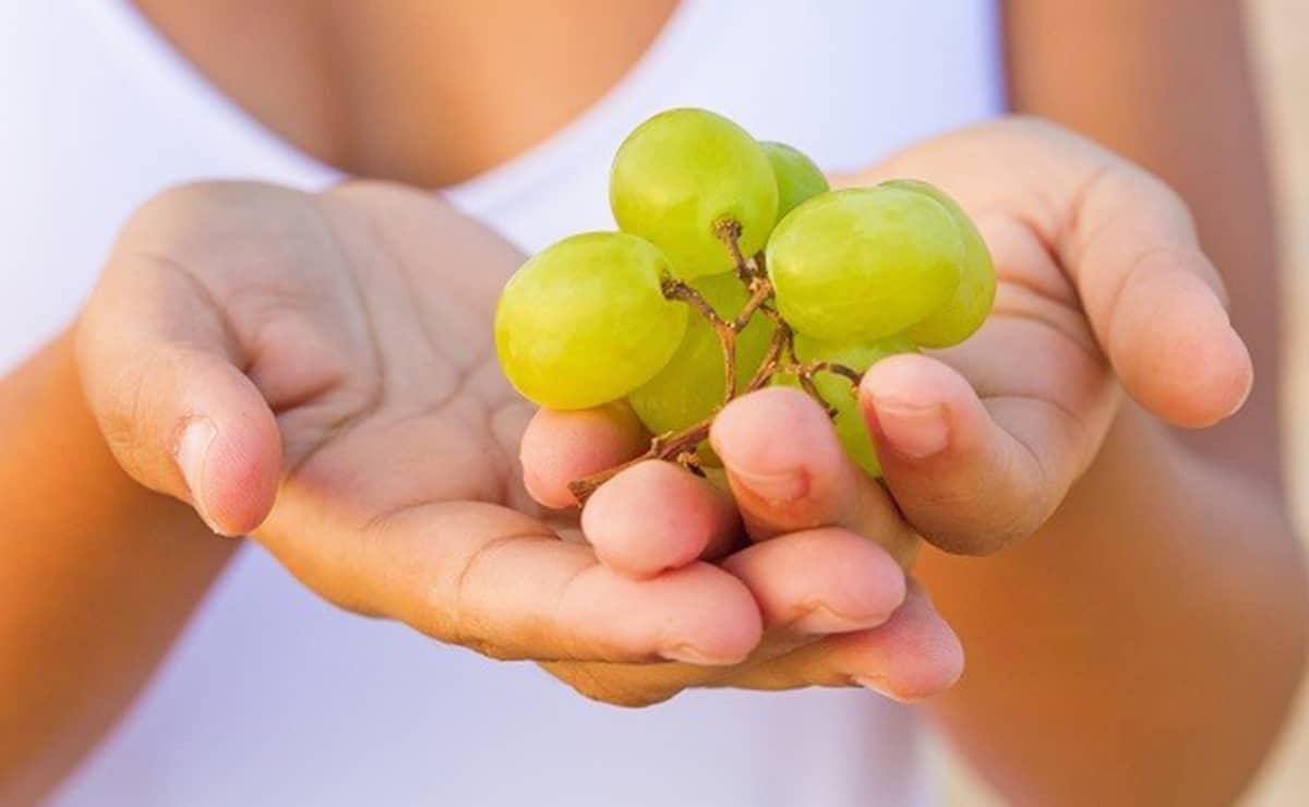 Mujer tomando uvas vitamina H