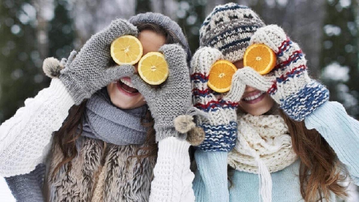 Dos niñas con naranja y limón con vitamina C