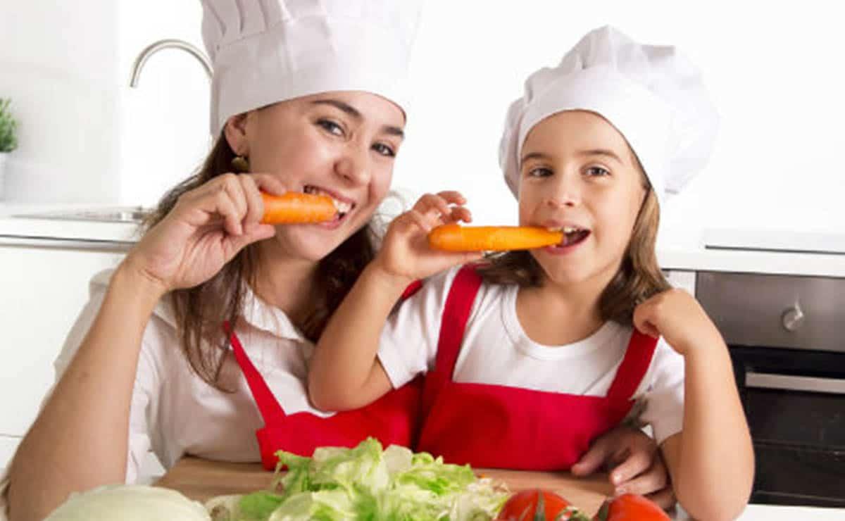 Madre e hija comiendo zanahoria