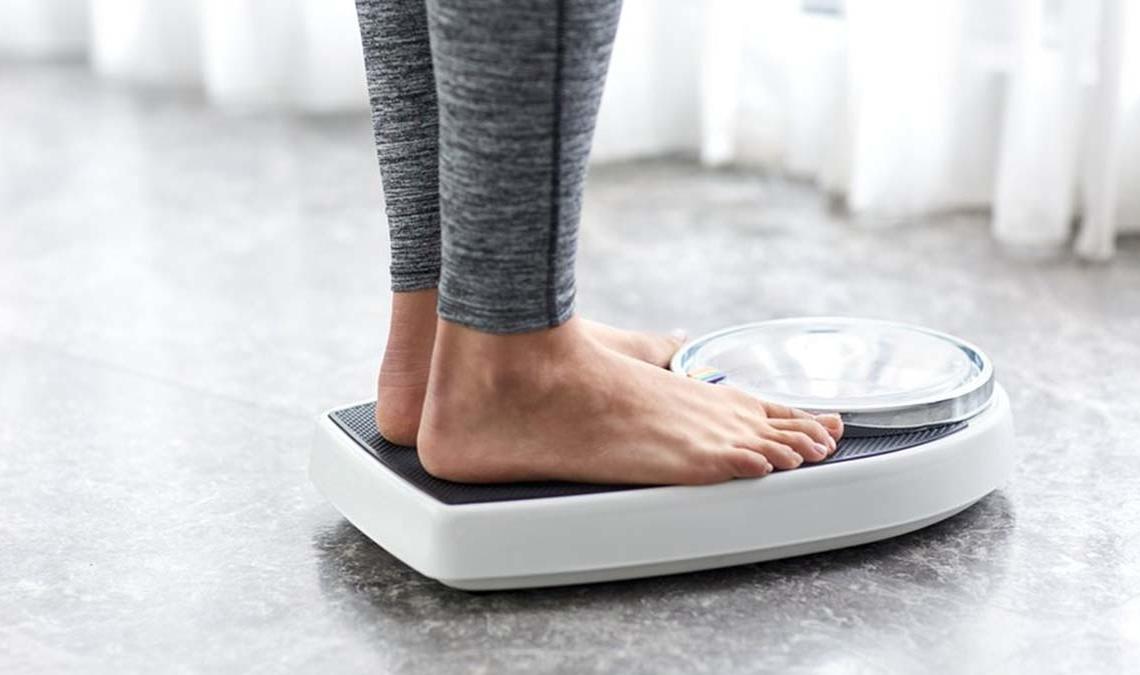 Una persona pesándose para comprobar si logra bajar de peso