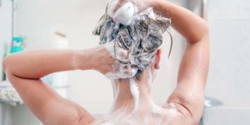 Una mujer lavándose el pelo con el nuevo champú de Mercadona