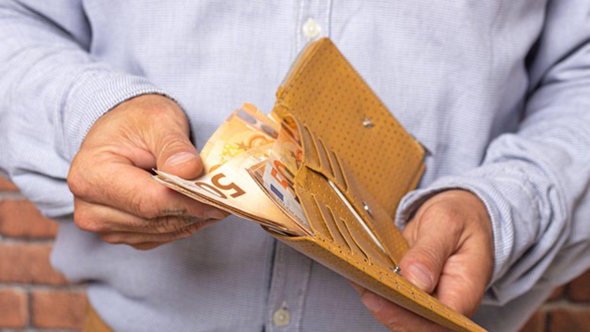 Persona sacando dinero pensiones de la cartera