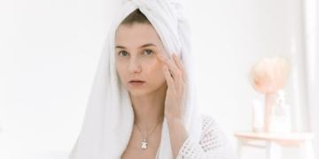 mujer aplicando crema sobre su piel