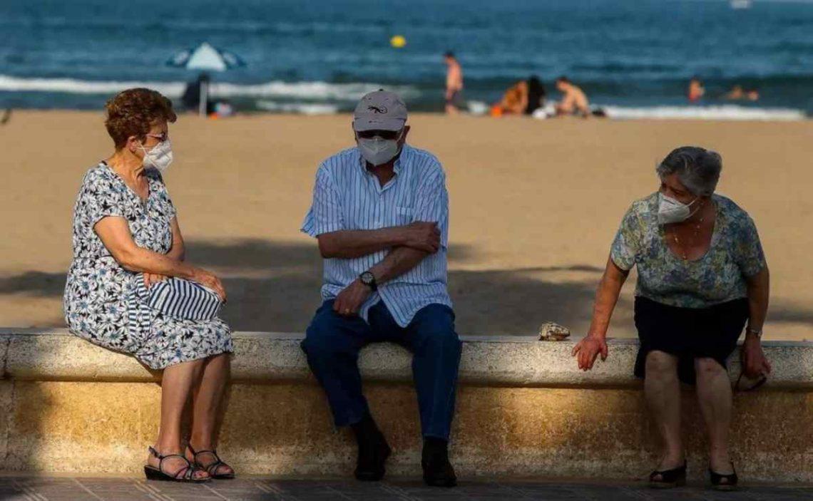 Turismo Imserso: Tres personas mayores descansan en el paseo marítimo de la playa de la Malvarrosa